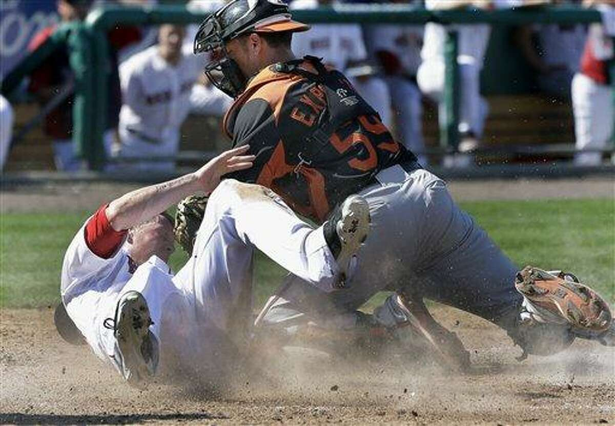 Boston Red Sox's Jeremy Hazelbaker slides safely into home to score on a single by Jonathan Diaz as Baltimore Orioles catcher Luis Exposito puts the tag on in the eighth inning of an exhibition spring training baseball game in Fort Myers, Fla., Tuesday, March 19, 2013. (AP Photo/Elise Amendola)