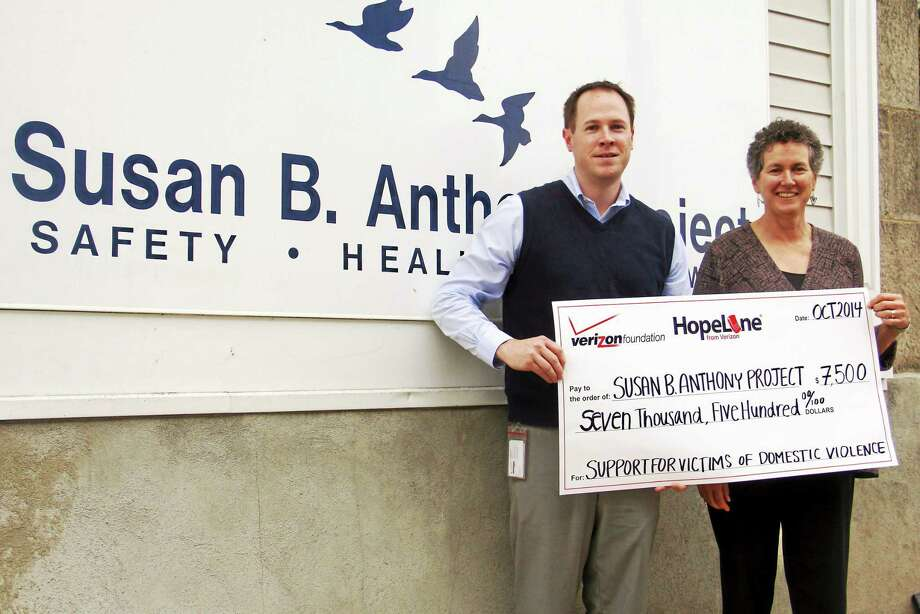 Michael Murphy, spokesperson for Verizon Wireless, holds a check for $7,500 alongside Susan B. Anthony Project Executive Director Barbara Spiegel Thursday outside the project's headquarters in Torrington. Photo: Esteban L. Hernandez — The Register Citizen