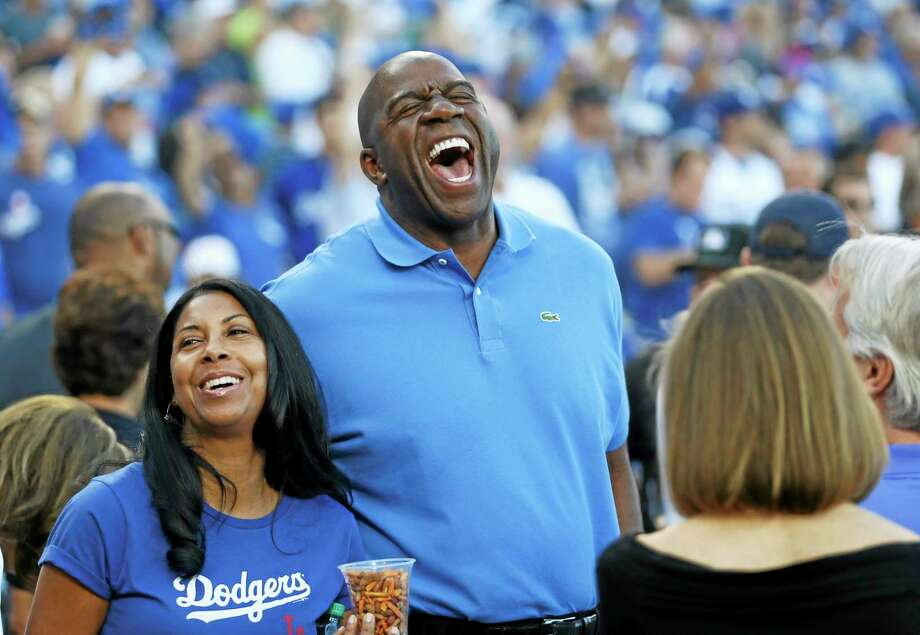 Los Angeles Dodgers owner Magic Johnson, here at Game 3 of the National League division series against the Atlanta Braves, will not return to ESPN as an NBA analyst. Photo: Danny Moloshok — The Associated Press  / FR161655 AP