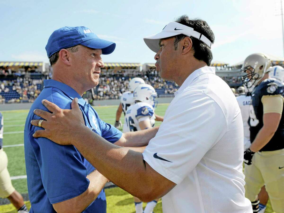 Navy head coach Ken Niumatalolo, right, meets with Air Force head coach Troy Calhoun, left, after Saturday's football game in Annapolis, Md.