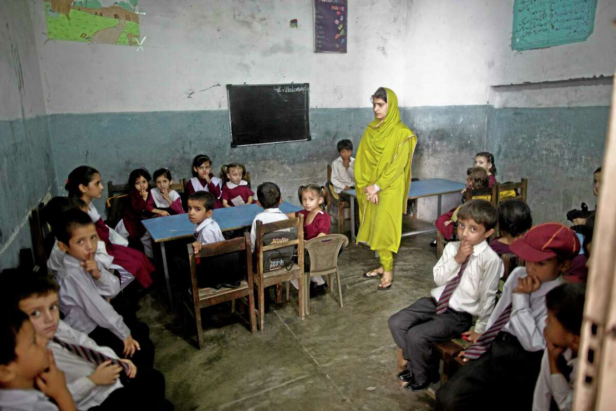 Pakistani school children sit in their classroom during a special class to commemorate the anniversary of Malala Yousufzai's shooting by Taliban, at a school in Rawalpindi, Pakistan, Wednesday, Oct. 9, 2013. One year after a Taliban bullet tried to silence Malala's demand for girls' education, she has published a book and is a contender for the Nobel Peace Prize. But the militants threaten to kill her should she dare return home to Pakistan, and the principal at her old school says that as Malala's fame has grown, so has fear in her classrooms. (AP Photo/Muhammed Muheisen)