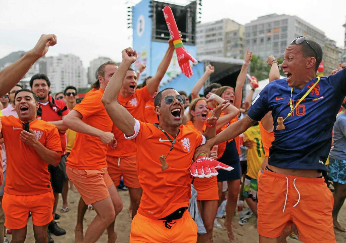 Soccer fans, decked out in orange, the Netherlands' national team color, celebrate the first goal scored by Leroy Fer, while watching a live broadcast of the group B World Cup match between Chile and Netherlands, inside the FIFA Fan Fest area on Copacabana beach, in Rio de Janeiro, Brazil, Monday, June 23, 2014. Netherlands won 2-0, taking the top spot in group B. (AP Photo/Leo Correa)