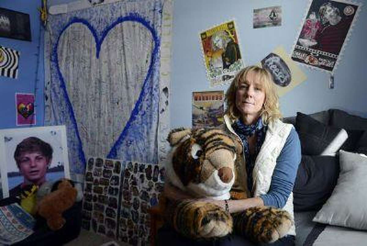 Louise Ingalls holds her son's stuffed-animal tiger on his bed at her home in Eagle on Wednesday. Her son, Taft Conlin, 13, died Jan. 22, 2012, in an inbounds avalanche at the Vail Resort. After Taft's death, his classmates filled a sheet, left, with thoughts and prayers that still hangs in his room. (Andy Cross, The Denver Post)