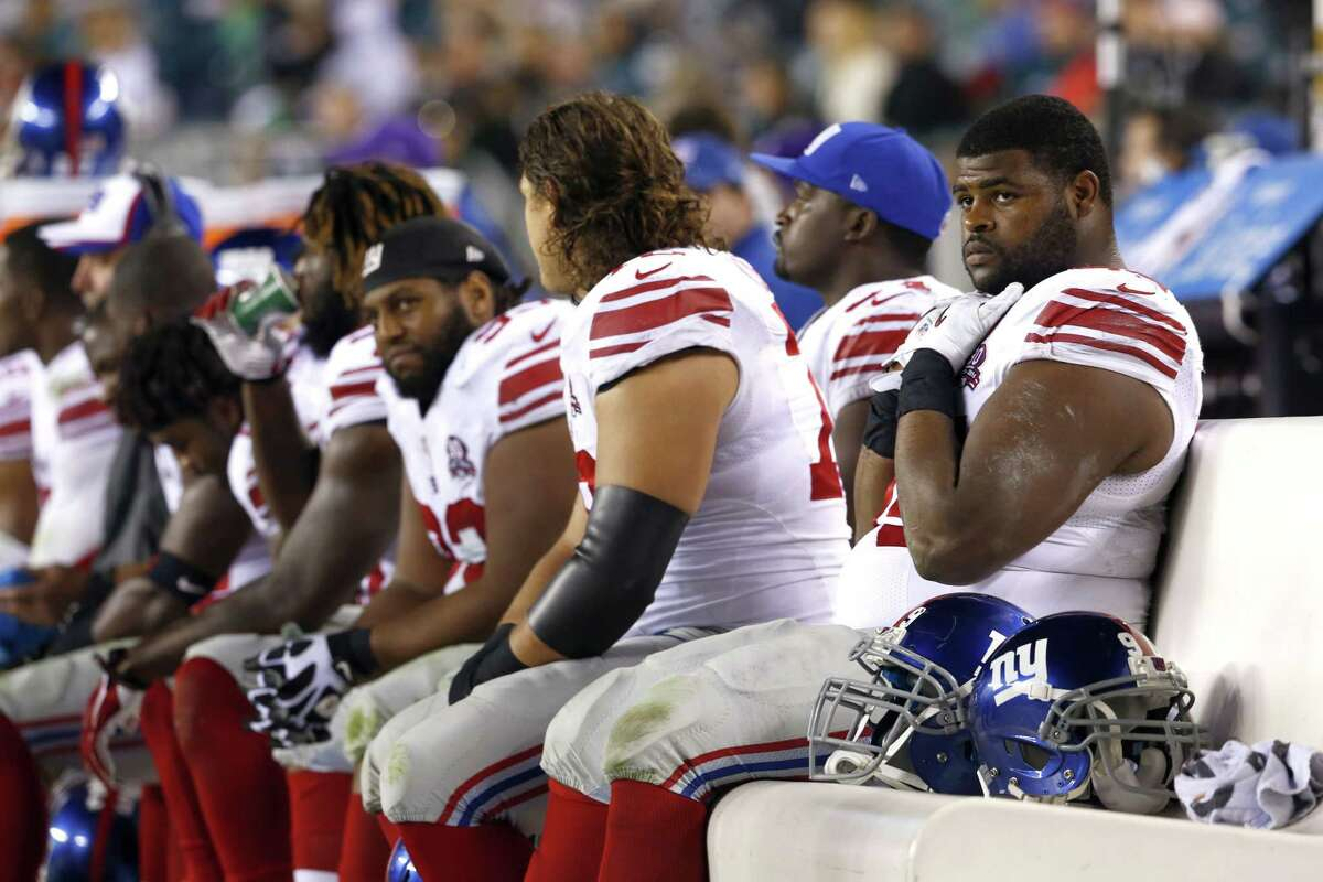 New York Giants defensive tackle Johnathan Hankins, right, sits on the bench with teammates during the second half of Sunday's 27-0 loss to the Eagles in Philadelphia.