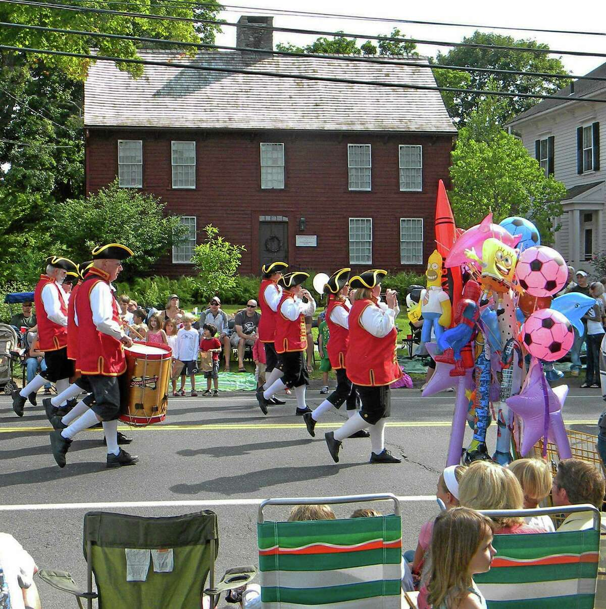 In this Sept. 7, 2009, photo, a fife-and-drum band in colonial-era uniforms marches past a souvenir seller and spectators during the Labor Day parade in Newtown, Conn. The parade has been a town fixture since Sept. 3, 1962. The town's upcoming 2013 parade faced for the first time calls and emails from regulars, folks who always marched, concerned about the most basic decision of all_how to proceed with a parade this year, nearly nine months after shootings at Sandy Hook Elementary School left 26 dead, 20 of them children. (AP Photo/Chris Sullivan)