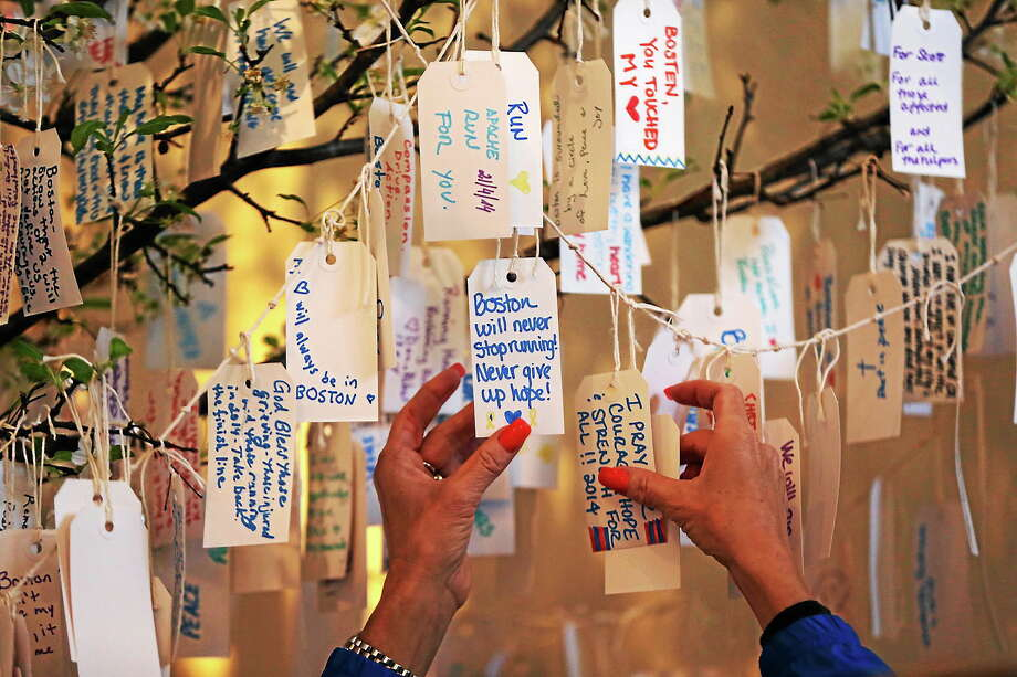 "A visitor hangs a message on a tree at the ""Dear Boston"" exhibit at the Boston Public Library on April 20, 2014 in Boston. The exhibit features a collection of items from the marathon bombing memorial. Photo: AP Photo/Robert F. Bukaty  / AP"