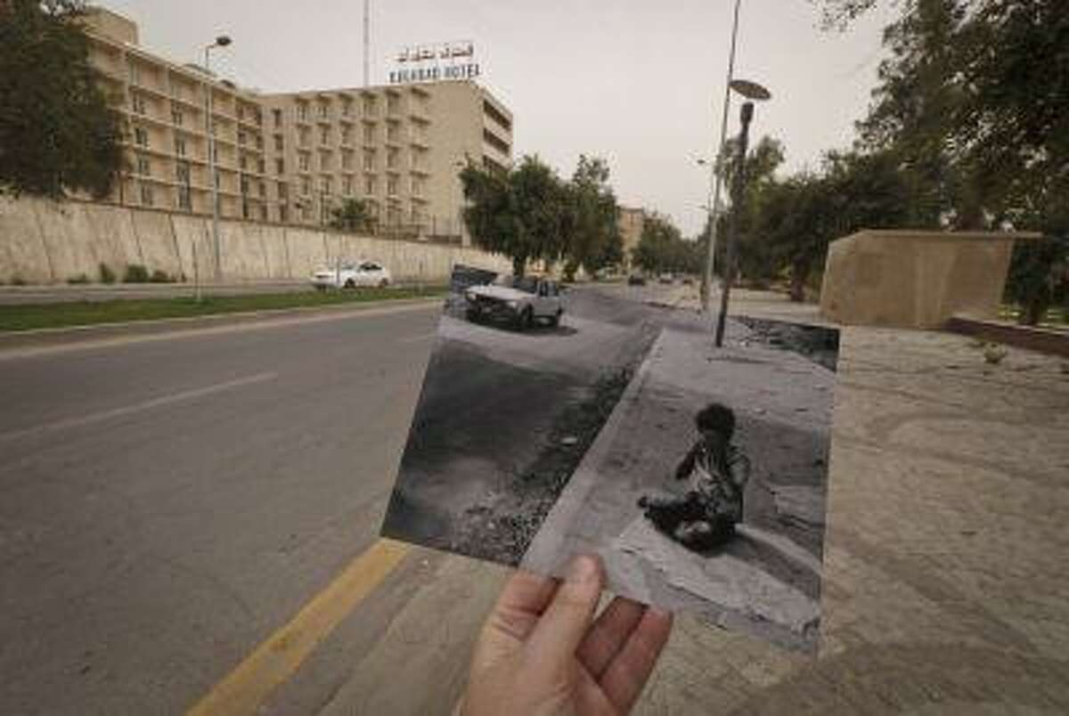 This March 12 photo shows a general view of Abu Nawas Street in Baghdad, Iraq, at the site of a photograph of Iraqi orphan Fady al-Sadik waking on the street, taken by photographer Maya Alleruzzo in April, 2003. The park that runs along Abu Nawas Street, named for an Arabic poet, is now a popular destination for families who are drawn by the manicured gardens, playgrounds and restaurants famous for a fish called mazgouf. Ten years ago, the park was home to a tribe of children orphaned by the war and was rife with crime.