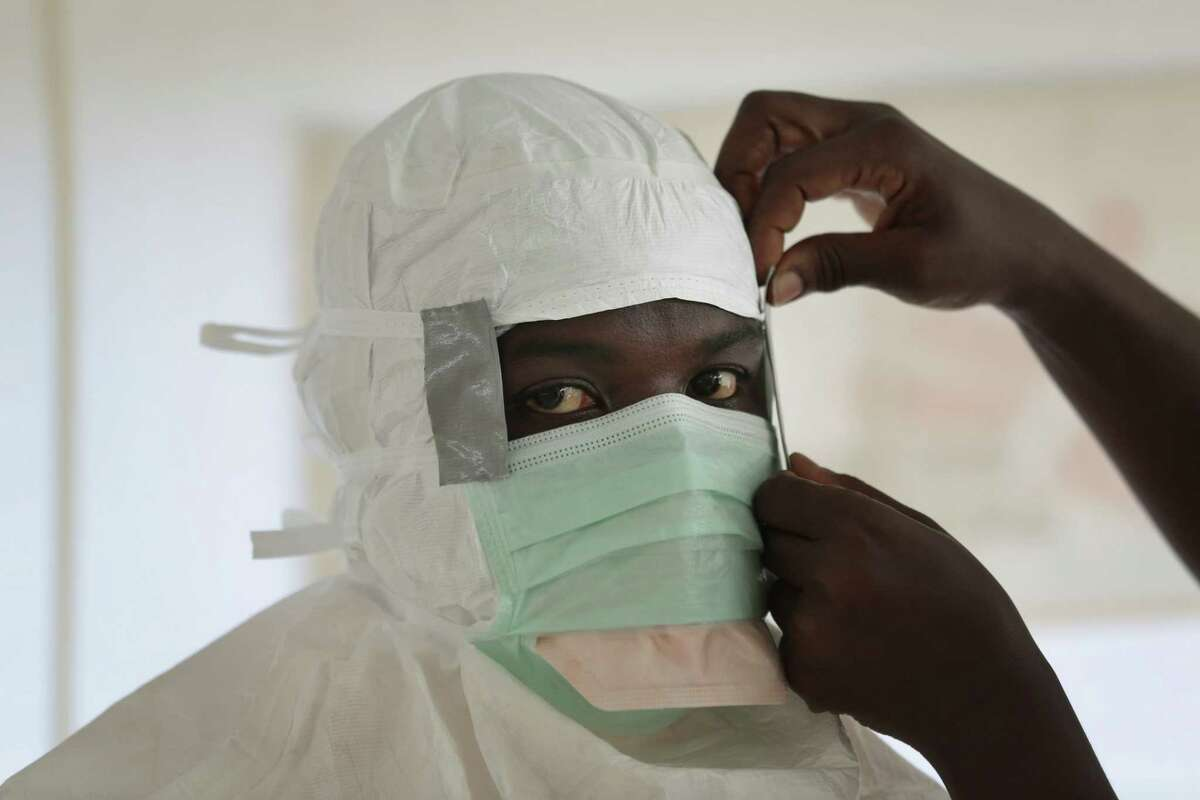 FILE - In this Monday, Sept. 29, 2014, file photo a MSF (Medecins Sans Frontieres) nurse gets prepared with Personal Protection Equipment before entering a high risk zone of MSF's Ebola isolation and treatment centre in Monrovia, Liberia. Ebola has killed more than 4,500 people in West Africa and wreaked havoc on the region, but some Africans see a bright side: The virus has been limited to five countries. It has even been beaten back in two of those countries. (AP Photo/Jerome Delay, File)