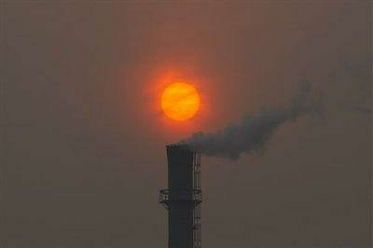 Smoke billows from the chimney of a heating plant as the sun sets in Beijing in this file photo dated Feb. 13, 2012.