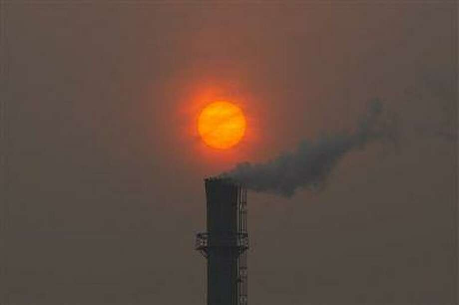 Smoke billows from the chimney of a heating plant as the sun sets in Beijing in this file photo dated Feb. 13, 2012. Photo: AP / ap