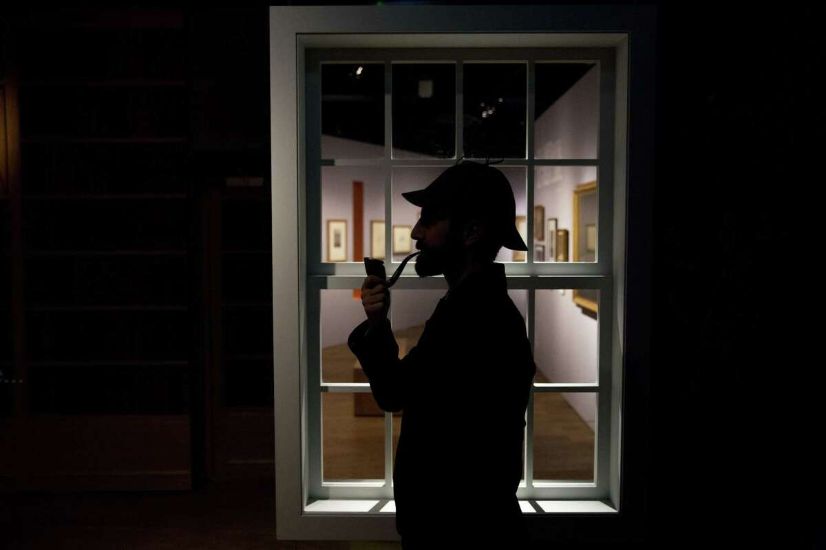 """Curator Timothy Long is silhouetted as he poses for photographers with a Sherlock Holmes style pipe and deerstalker hat beside an internal window forming part of the exhibition """"Sherlock Holmes: The Man Who Never Lived and Will Never Die"""" at the Museum of London in London, Thursday, Oct. 16, 2014. The exhibition, which opens to the public on Friday, is the largest on the fictional detective created by Scottish author Sir Arthur Conan Doyle to be held in the UK for 60 years (AP Photo/Matt Dunham)"""