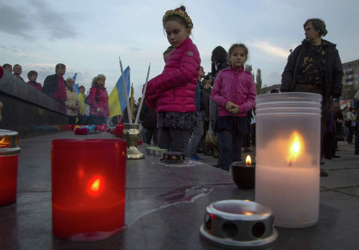 Children look at candles during a rally in memory of civilians killed in the town of Mariupol, eastern Ukraine Wednesday, Oct. 15, 2014. Local authorities in Mariupol, a government-controlled city on the Black Sea, said seven civilians were killed and 17 injured Tuesday by shelling in the nearby village of Sartana. (AP Photo/Dmitry Lovetsky)