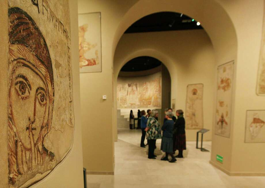 People stand near a 9th century wall painting of Saint Anna, left, in an enhanced exhibition of Christian-era paintings from Faras, Sudan, at the National Museum in Warsaw, Poland, on Thursday, Oct. 16, 2014. Polish archaeologists found and saved the paintings in the 1960s in a UNESCO action before they could be flooded by the New Aswan Dam reservoir. Some of the found paintings were brought to the National Museum in Warsaw, the others are in Khartoum, Sudan. (AP Photo/Czarek Sokolowski) Photo: AP / AP