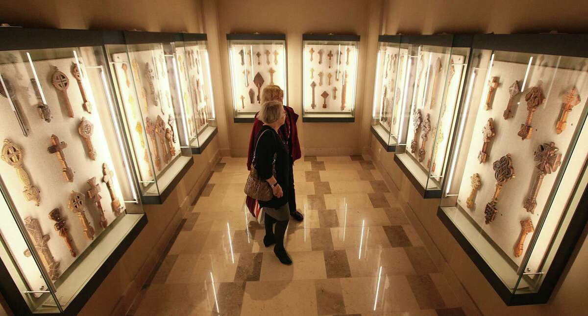 Visitors walk through an exhibition of various forms of Christian crosses at the National Museum in Warsaw, Poland, on Thursday, Oct. 16, 2014. (AP Photo/Czarek Sokolowski)
