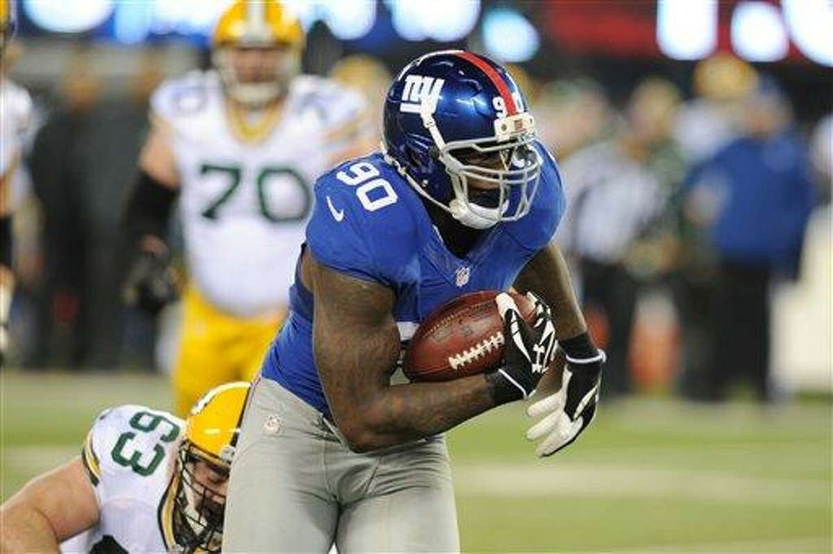 New York Giants defensive end Jason Pierre-Paul (90) runs back a fumble recovery during the first half of an NFL football game Sunday, Nov. 25, 2012 in East Rutherford, N.J. (AP Photo/Bill Kostroun)