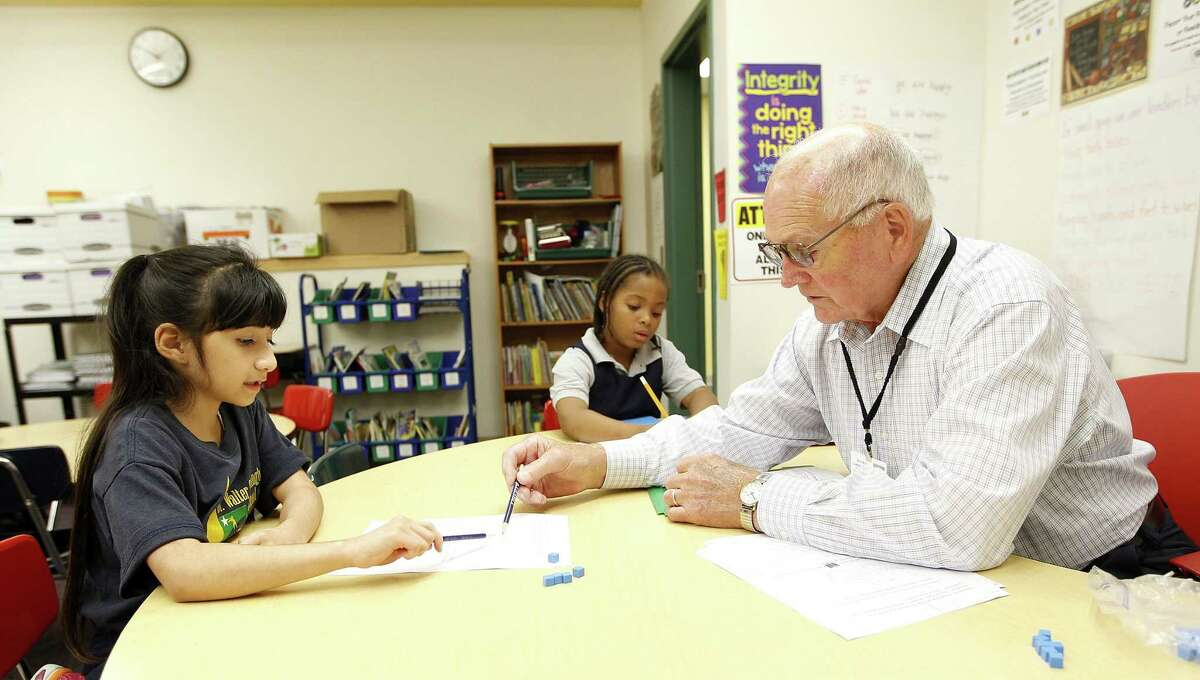 In this photo taken on Sept. 26, 2014, retired teacher Richard Halstead works on math with Evelin Montano, left, and Denia Jones while substitute teaching at Dr. Walter Cunningham School for Excellence in Waterloo, Iowa.