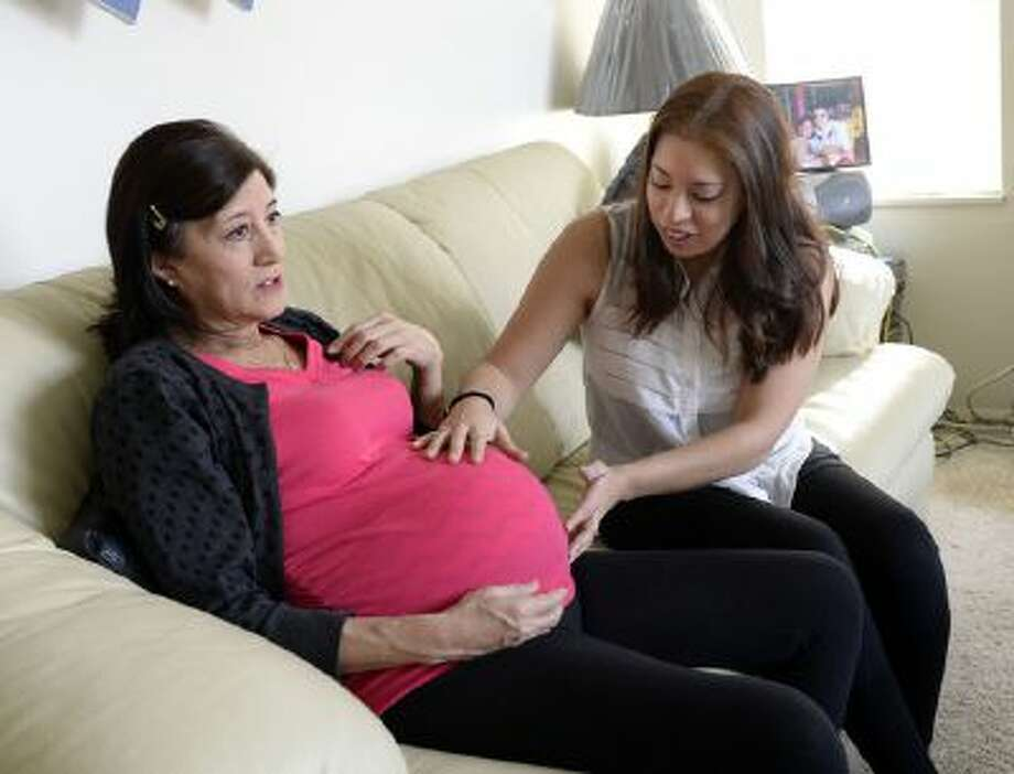 Lorena McKinnon, right, has never been able to bring a baby to term so her 58-year-old mother Julia Navarro is having the baby for her. They are about eight months into the pregnancy. Lorena feels her mother's womb for movement of her daughter that will be born in about a month. Photo: TRIB / (C) 2013 The Salt Lake Tribune, MediaNews Group