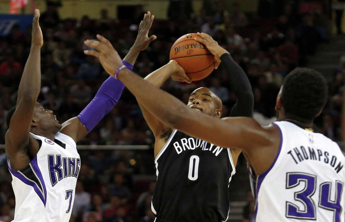 Brooklyn Nets guard Jarrett Jack tries shoots over the Sacramento Kings' Darren Collison, left, and Jason Thompson during an exhibition game Wednesday in Beijing, China.
