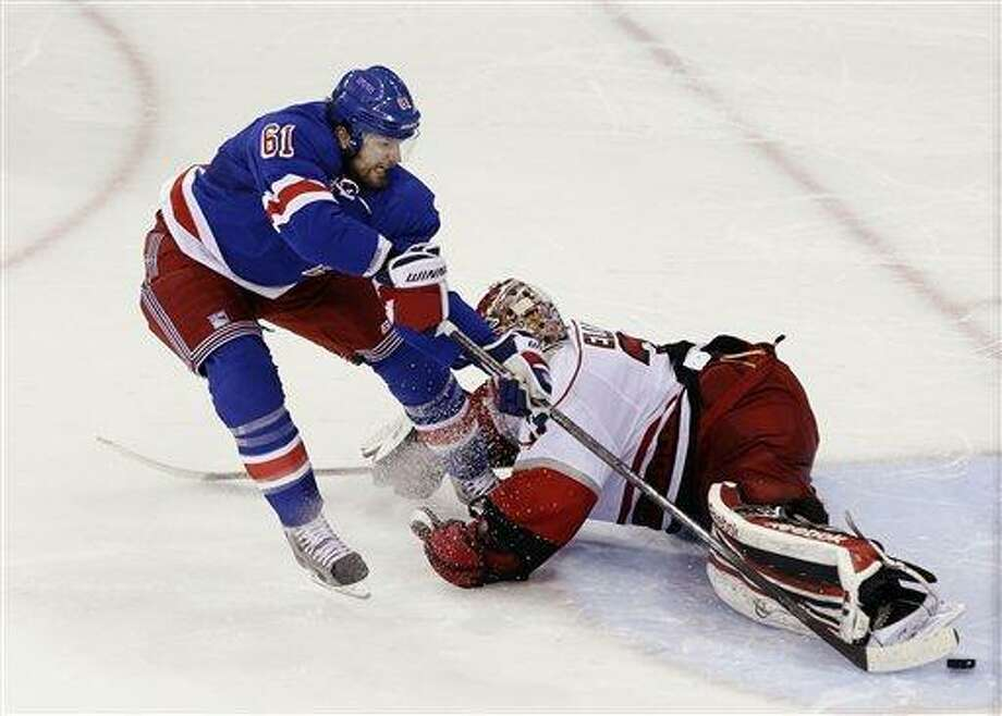 New York Rangers' Rick Nash (61) shoots the puck past Carolina Hurricanes goalie Dan Ellis (31) during the shootout of an NHL hockey game, Monday, March 18, 2013, in New York. The Rangers won 2-1. (AP Photo/Frank Franklin II) Photo: ASSOCIATED PRESS / AP2013