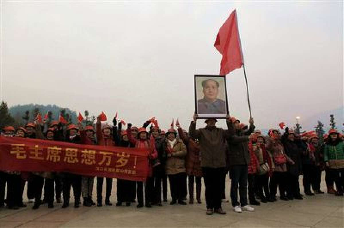 People wave flags and hold a banner as they pose for a group photo on a square near a statue of the late Communist leader Mao Zedong in Shaoshan, Mao's hometown, in south China's Hunan province.