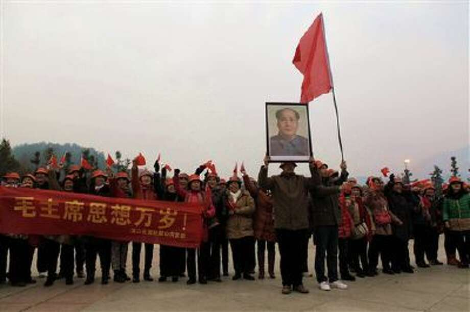 People wave flags and hold a banner as they pose for a group photo on a square near a statue of the late Communist leader Mao Zedong in Shaoshan, Mao's hometown, in south China's Hunan province. Photo: AP / CHINATOPIX