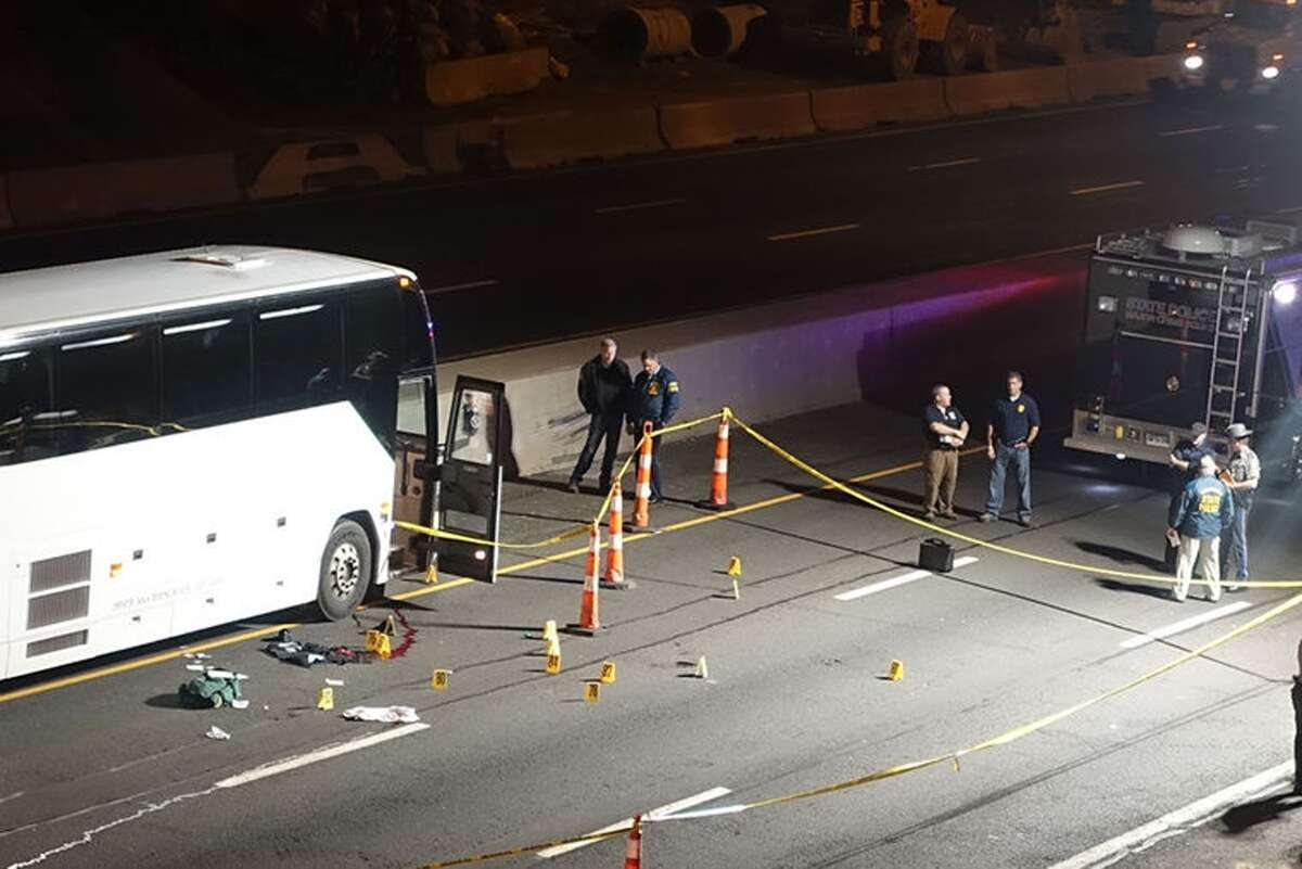 Law enforcement investigates the scene of a stabbing aboard a tour bus late Tuesdayin Norwalk. A man who stabbed passengers on the casino-bound tour bus on Interstate 95 was fatally shot by a state trooper, state police said Wednesday.