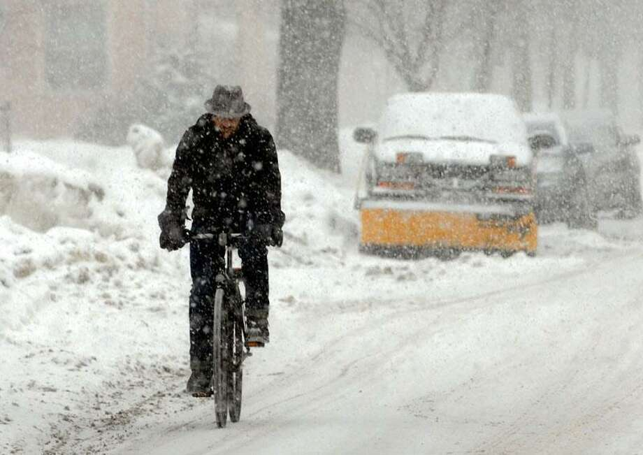 Another snowtorm doesn't stop the residents of the East Rock neighborhood in New Haven. Yale researcher Jon Arellano of New Haven is a Basque and doesn't let a little snow stop his bike ride to work. Photo by Mara Lavitt/New Haven Register1/26/11