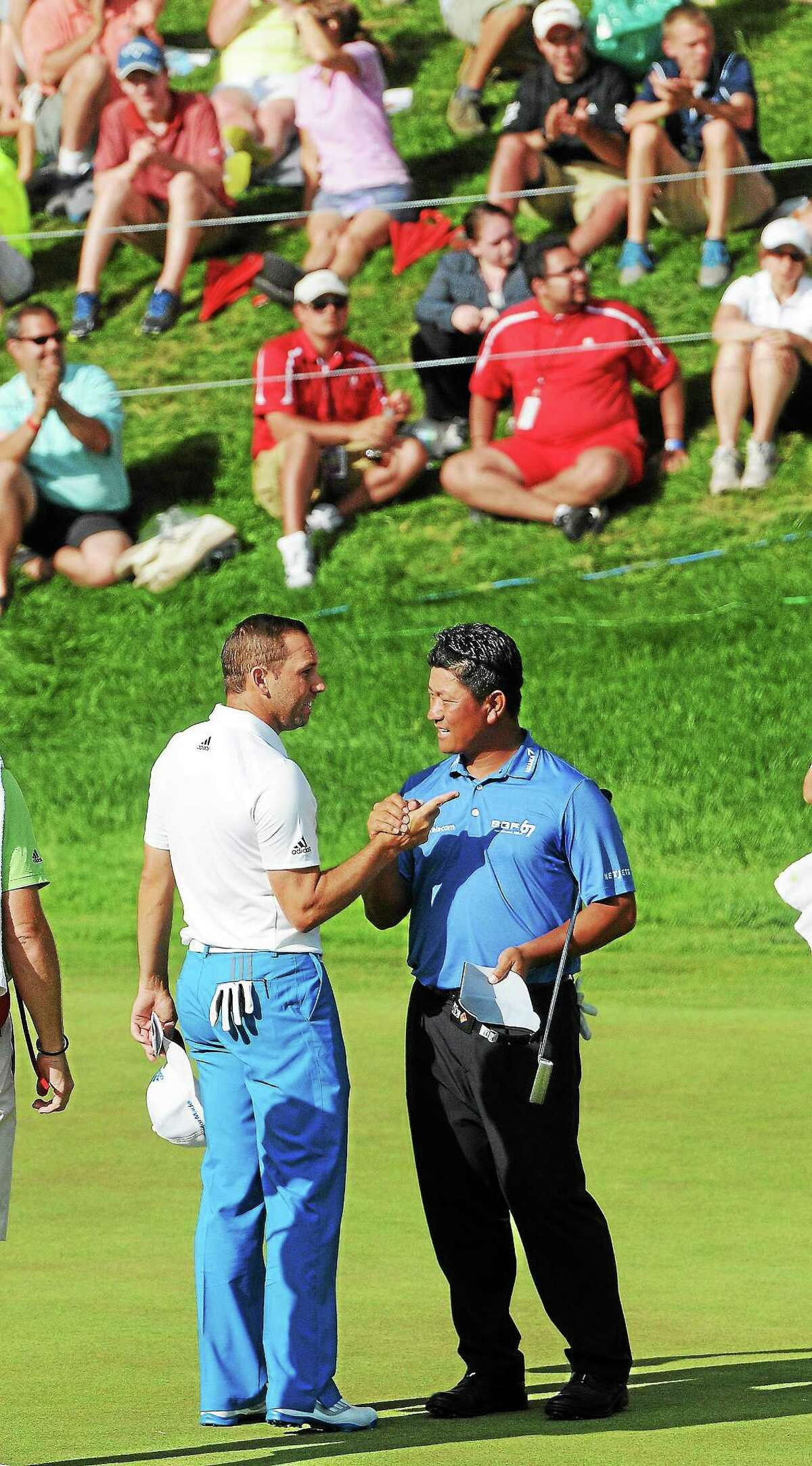 Sergio Garcia, left, and K.J. Choi shake hands after both finishing 14-under and tied for second at the Travelers Championship on Sunday at TPC River Highlands in Cromwell.