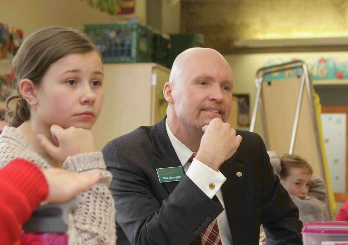 Paul McLaughlin, the outgoing director of the United Way of Northwest CT board, listens to student discussion along with Abigail Abbenante and Tara Garden during JA (Junior Achievement) in a Day at Litchfield Intermediate School in March 2013.