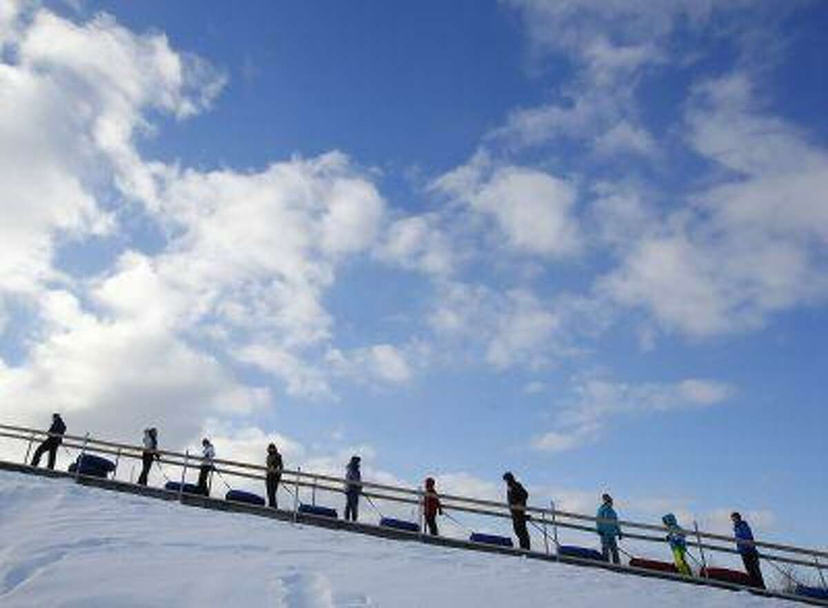 People ride a sky carpet up a toboggan hill in Rochester, New York, January 1, 2013. People around the world enjoyed the first day of the New Year outside with their family. (Reuters/Carlo Allegri)