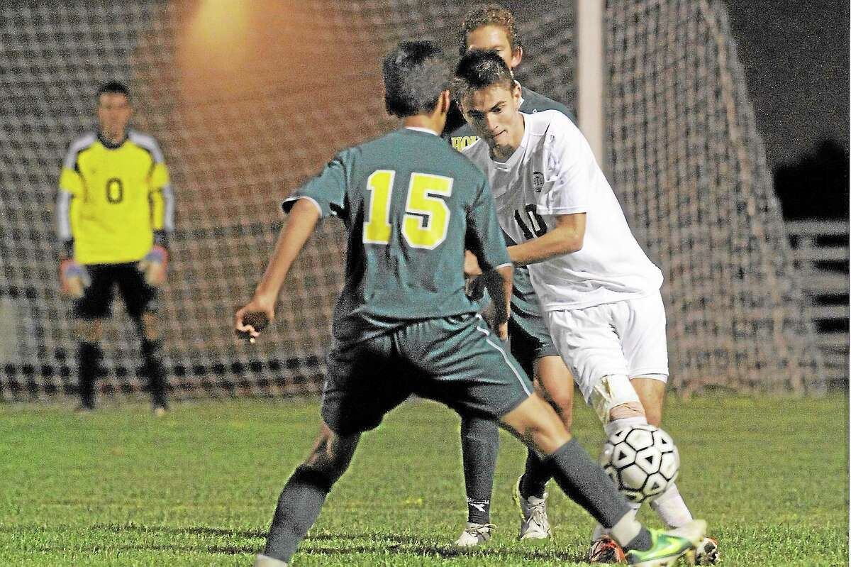 Laurie Gaboardi Register Citizen Torrington's Amar Suljic passes the ball past Holy Cross defender, Alex Matos in the Red Raiders 3-1 win against the Crusaders. Suljic scored the first goal of the game.