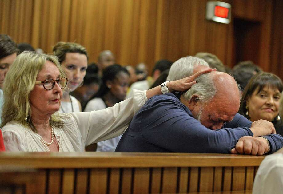 Reeva Steenkamp's father Barry Steenkamp, right, cries as he is comforted by his wife June, left, as they listen to proceedings during the third day of sentencing for Oscar Pistorius at the high court in Pretoria, South Africa, Wednesday, Oct. 15, 2014. Pistorius faces up to 15 years in prison after being convicted of culpable homicide, or negligent killing, for shooting Steenkamp, although he could also receive a suspended jail sentence and a fine. (AP Photo/Antoine de Ras, Pool) Photo: AP / POOL INDEPENDENT NEWSPAPERS
