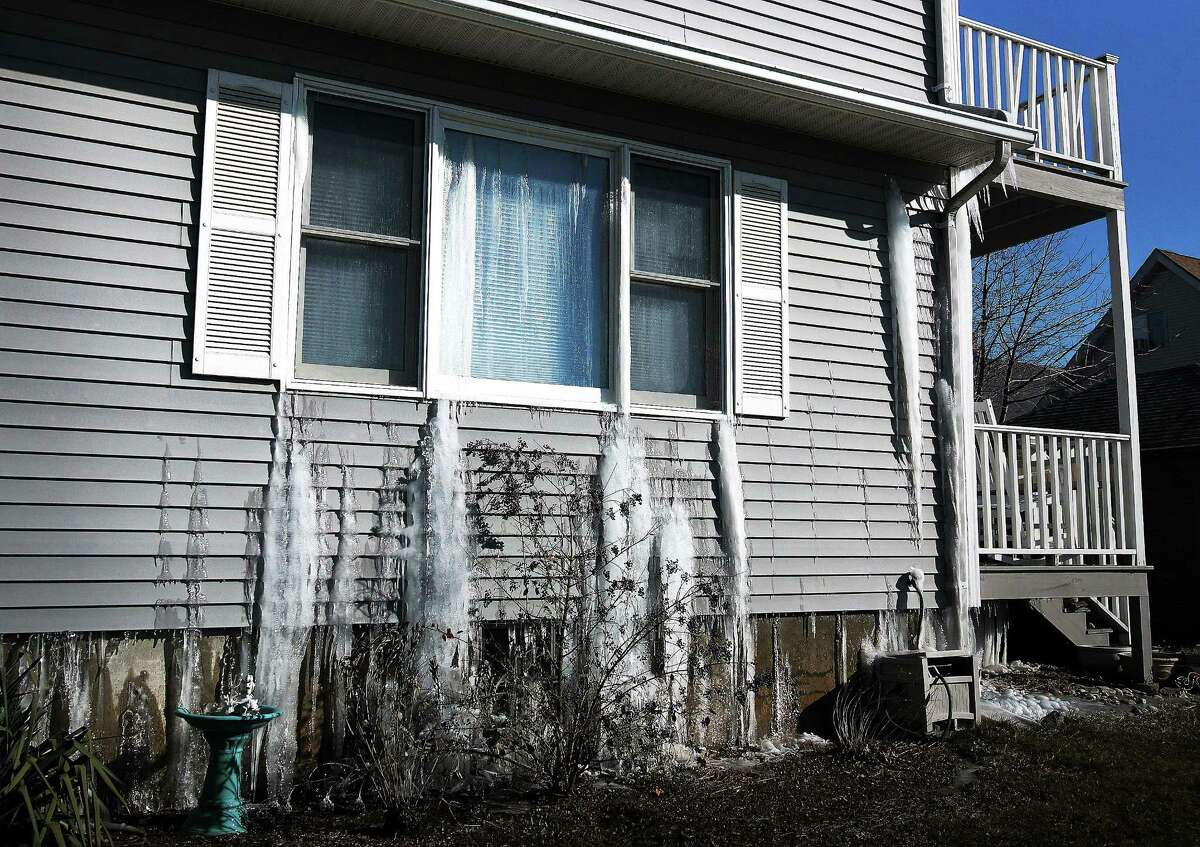 (Peter Casolino ó New Haven Register) Ice flows out of a 2-family house at Springdale Street and Buckingham Avenue in Milford after the pipes burst inside from the cold. pcasolino@NewHavenRegister