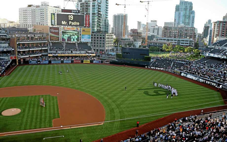 Padres players stand in right field observing 19 seconds of silence in honor of Hall of Fame player Tony Gwynn during ceremonies prior to Wednesday's game against the Seattle Mariners in San Diego. Gwynn died Monday of cancer at the age of 54. Photo: Lenny Ignelzi — The Associated Press  / AP