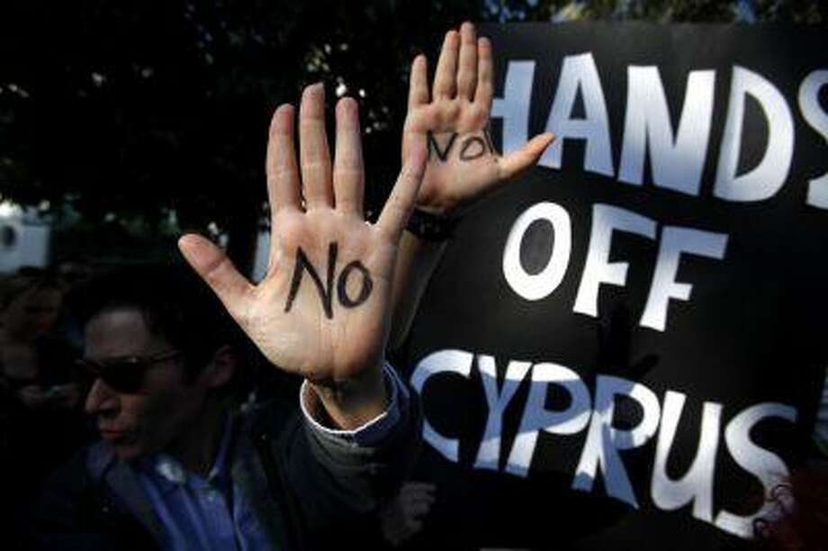 Protesters hold up their hands as they protest outside the parliament in capital Nicosia, Cyprus, on Monday. A vote on a bailout package for Cyprus that includes an immediate tax on all savings accounts has been postponed until Tuesday evening. (AP Photo/Petros Karadjias) Photo: ASSOCIATED PRESS / AP2013