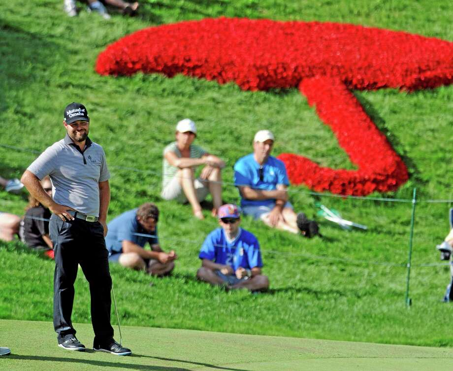 Ryan Moore smiles on the 18th green during the third round of the Travelers Championship on Saturday in Cromwell. Moore heads into Sunday at -13 with a 1-shot lead over Aaron Baddeley. Photo: Fred Beckham — The Associated Press  / FR153656 AP