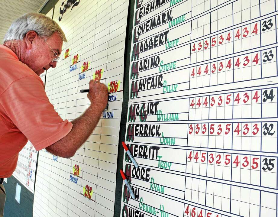 Calligrapher Dave Koenig writes the scores for each and every player at the Travelers Championship on a giant scoreboard near the 18th green. Photo: Mara Lavitt — Register  / Mara Lavitt