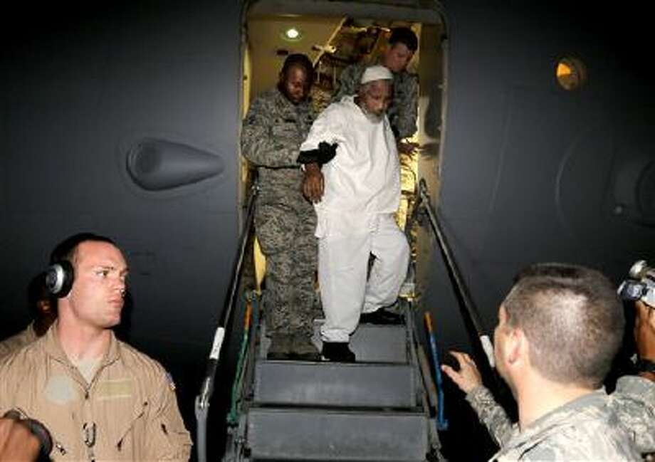 Ibrahim Idris is escorted off a U.S. military plane by troops after his release from Guantanamo Bay. Photo: AP / AP