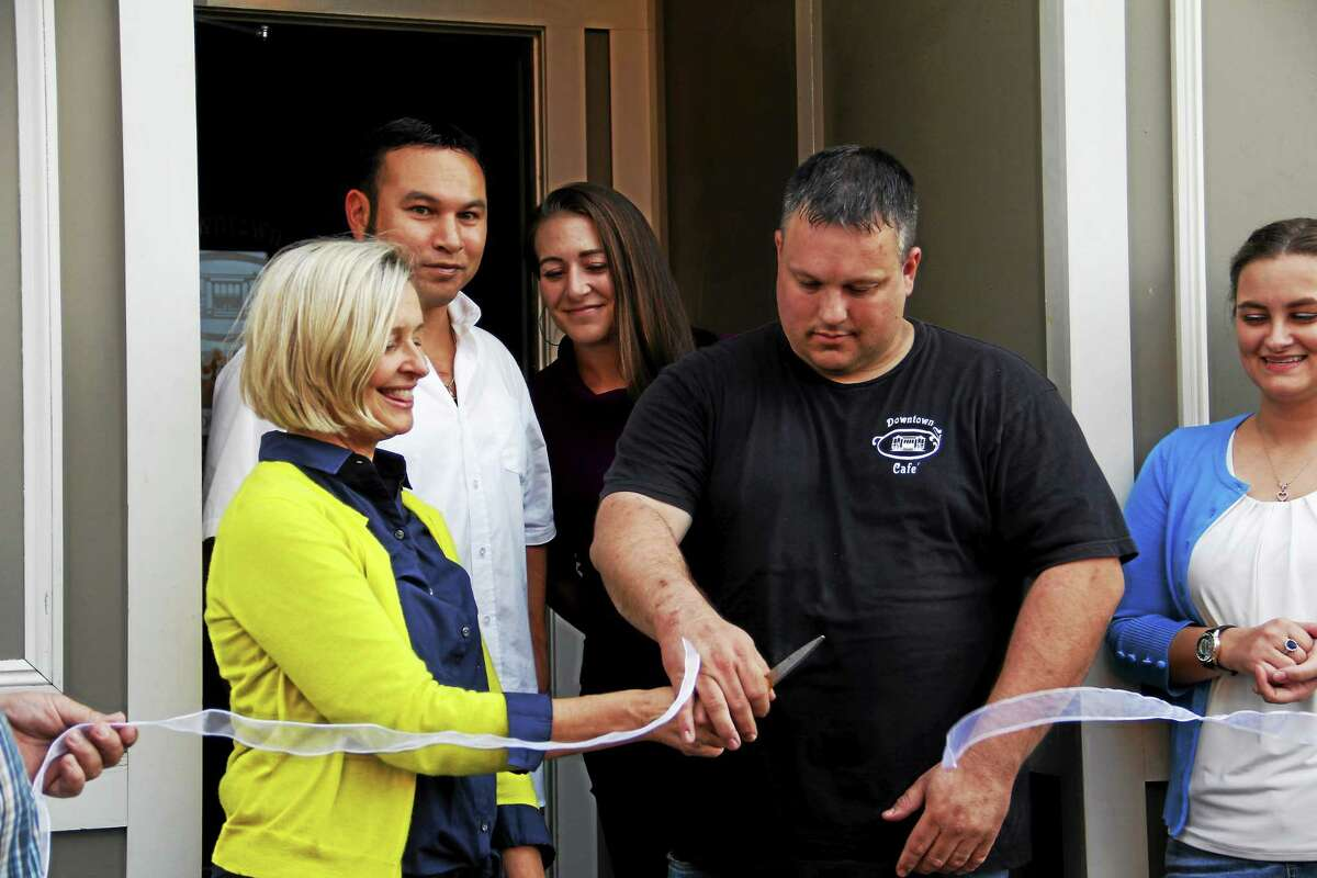 Rose Ponte, left, helps cut the ribbon at the grand opening of the Downtown Cafe on Water Street in Torrington.