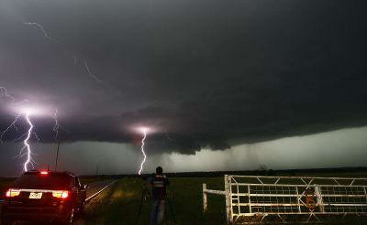 Cloud to ground lightning strikes near storm chasers during a tornadic thunderstorm in Cushing May 31, 2013.