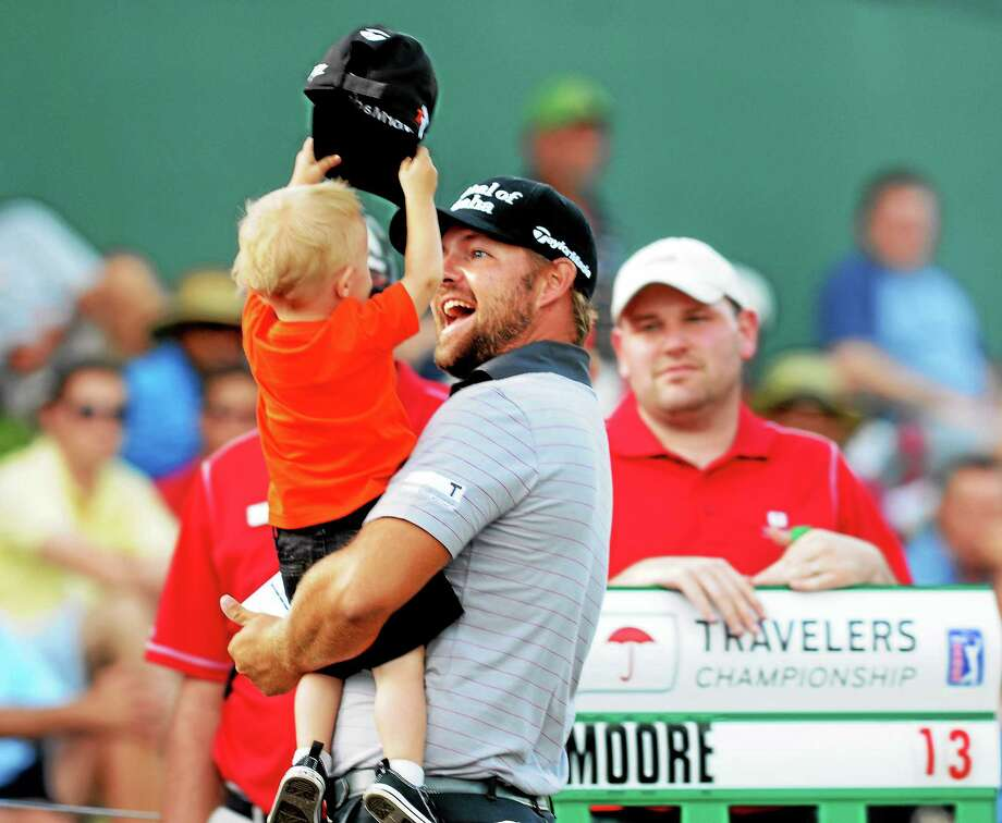 Travelers Championship third-round leader Ryan Moore is greeted by his 20-month-old son, Tucker, after parring the 18th hole. Photo: Mara Lavitt — Register  / Mara Lavitt