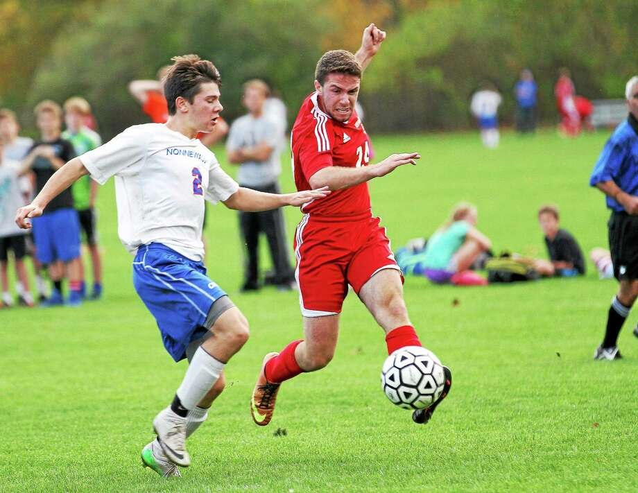 Northwestern's Steven Lee, right, takes a shot on goal in front of Nonnewaug's Luke Molinaro on Tuesday. Photo: Marianne Killackey — Special To Register Citizen  / 2014