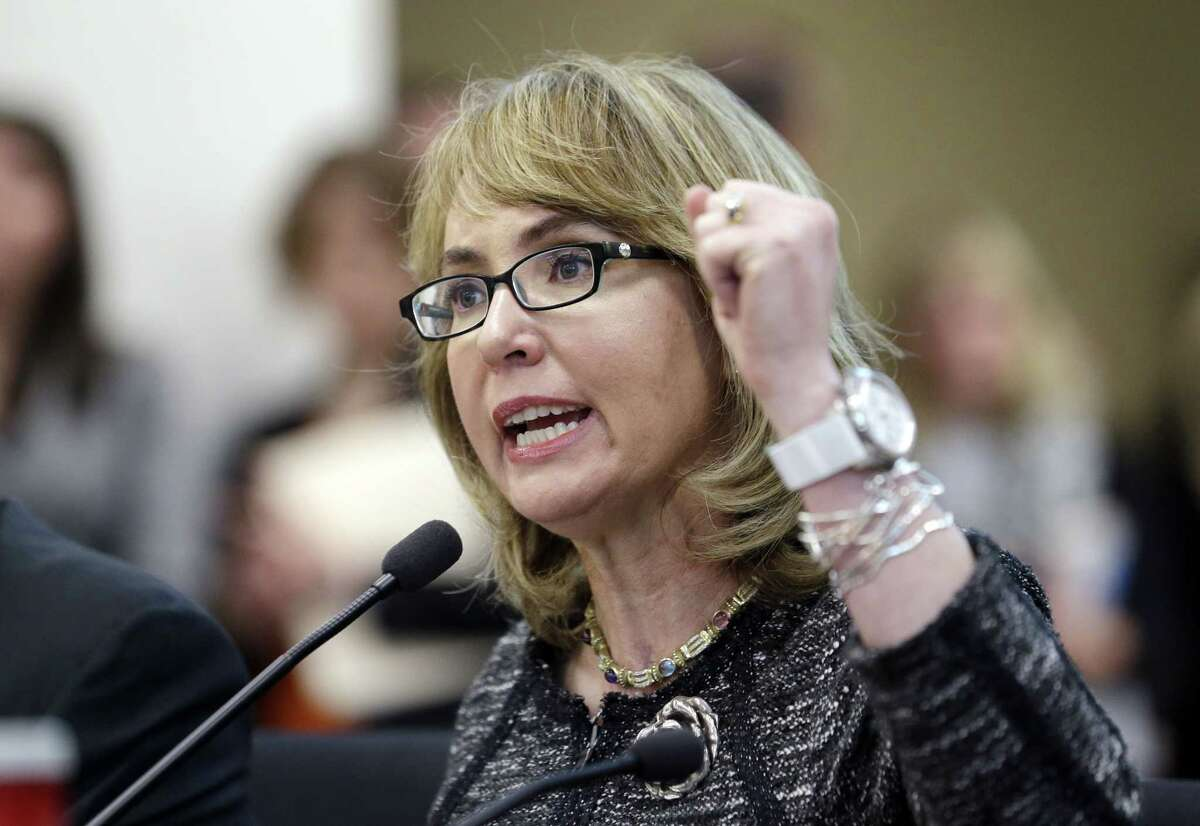 In this Jan. 28, 2014, file photo, former Arizona Congresswoman Gabrielle Giffords pumps her fist as she testifies before a Washington state House panel in Olympia, Wash. Giffords will begin a nine-state tour in Maine on Tuesday, Oct. 14, 2014, where she will advocate for tougher gun laws that she says will help protect women and families. Giffords, who was severely wounded by a gunman in 2011, will seek to elevate the issue of gun violence against women and push for state and federal action to make it more difficult for domestic abusers to get a hold of firearms.