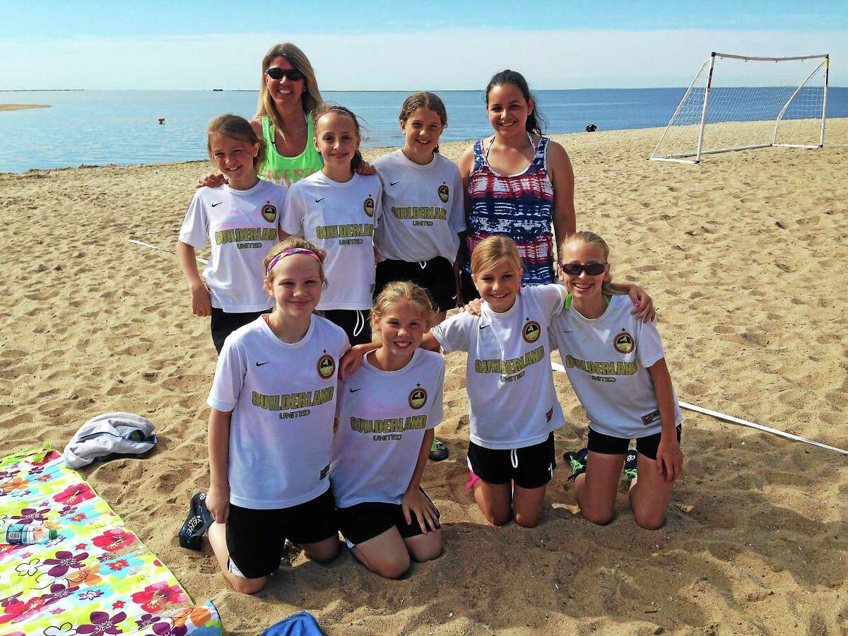 Coach Carmen Mulyca stands with her U-12 team from Guilderland, N.Y. The girls had already won their first game, 7-1.