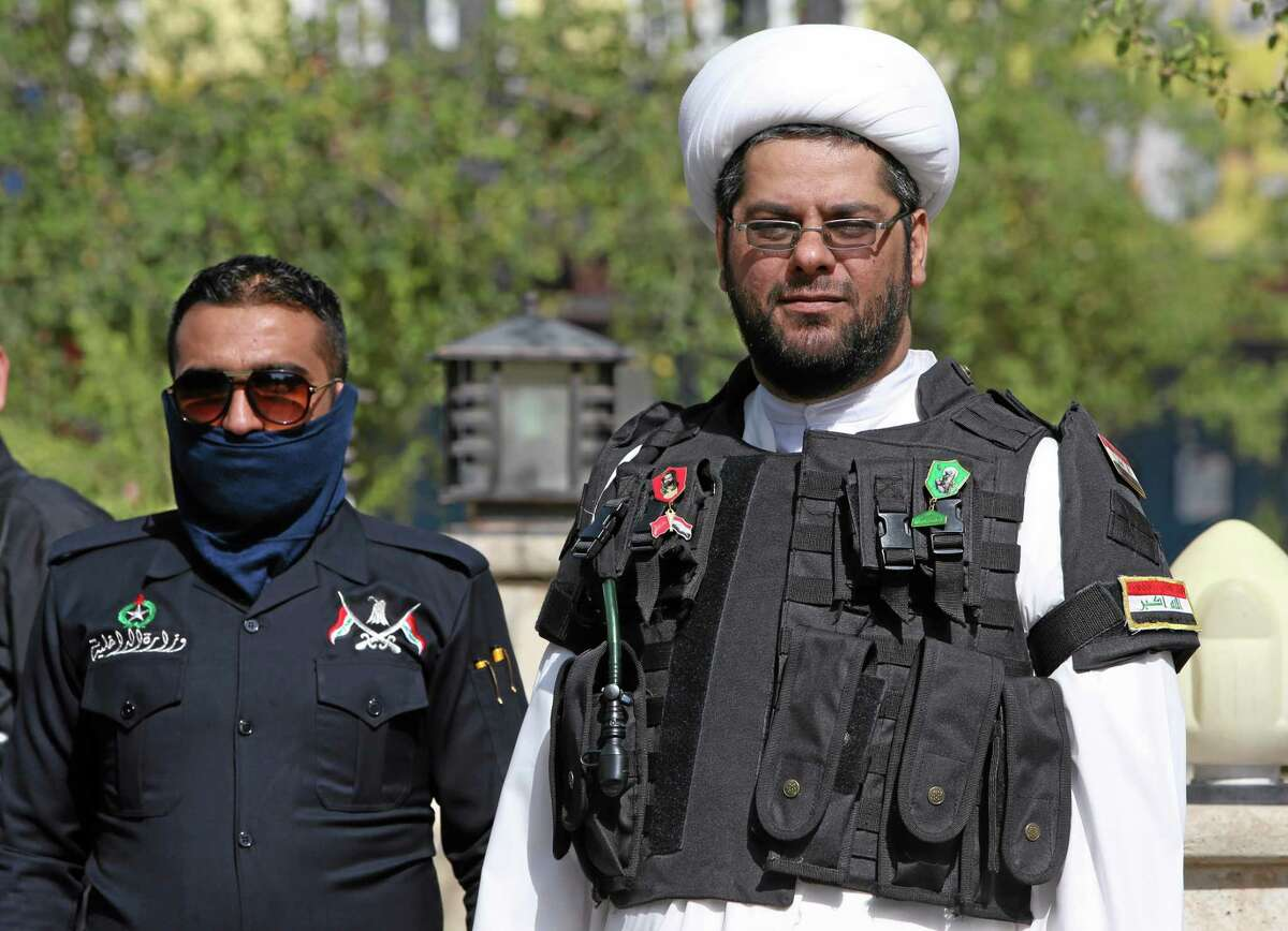 An Iraqi Shiite cleric, right, wears a military vest as he watches a parade of Shiite militiamen, in the mostly Kurdish northern oil rich province of Kirkuk, Iraq, Saturday June 21, 2014. Thousands of heavily-armed Shiite militiamen paraded through several Iraqi cities on Saturday as Sunni militants seized two strategically located towns in what appeared to be a new offensive in the western Anbar province. (AP Photo/Hussein Malla)