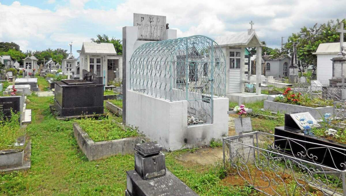 """The tomb of Rabbi Shalom Imanuel Muyal, who died of yellow fever in 1910, lays at Saint John the Baptist Cemetery in Manaus, Friday, June 20, 2014. Muyal is revered by Christians in Manaus as the """"Santo Judeu."""" Or, more simply, """"O Rabino."""" (AP Photo/Chris Lehourites)"""