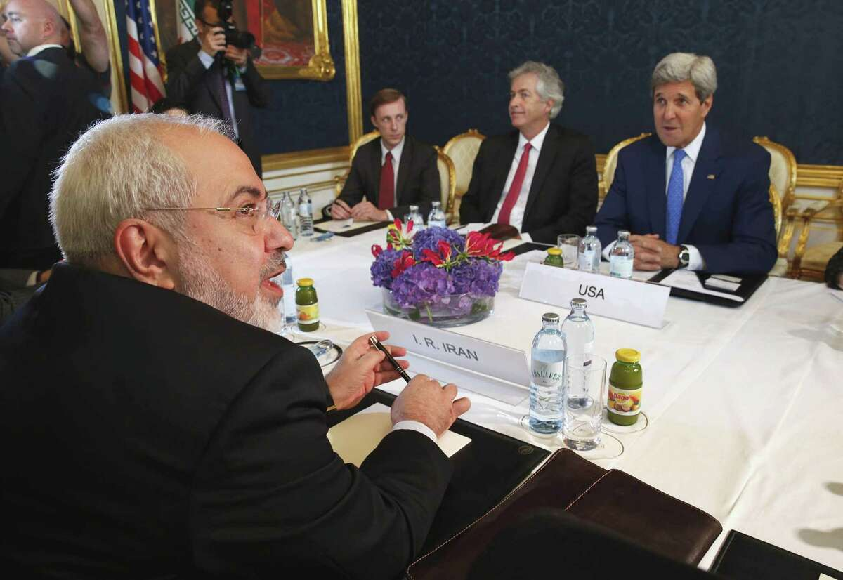 FILE - In this Monday, July 14, 2014 file photo, Iran's Foreign Minister Mohammad Javad Zarif, foreground left, holds a bilateral meeting with U.S. Secretary of State John Kerry, background right, on the second day of talks, in Vienna, Austria. With differences still unresolved and a Nov. 24 deadline for a deal nearing, Iran and the United States have a choice to make: Extend nuclear talks for the second time or face the risk of renewed confrontation and armed conflict. (AP Photo/Jim Bourg, Pool-File)