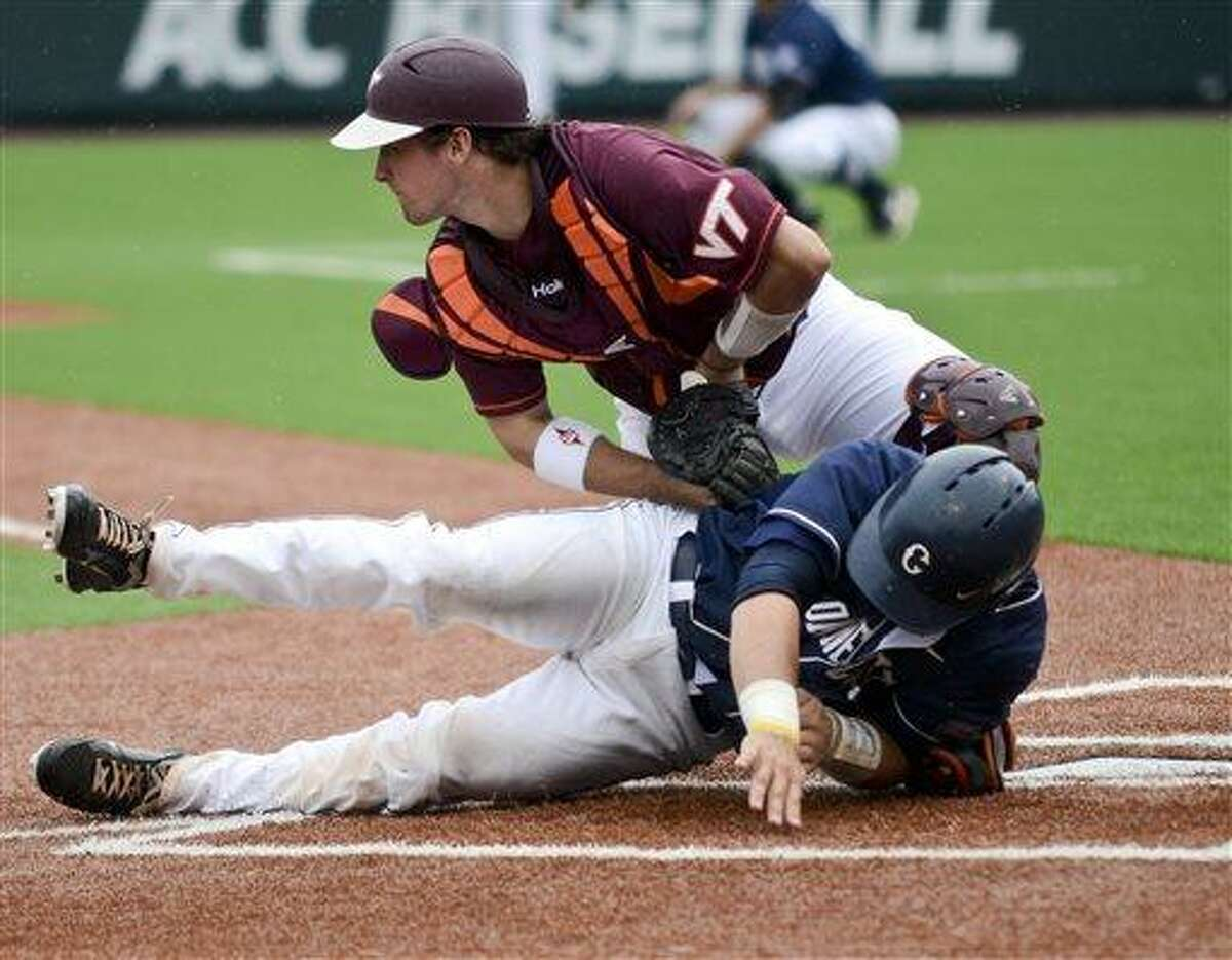 Virginia Tech's Chad Pinder, top, tags out UConn's Max McDowell at home during an NCAA college baseball tournament regional game at English Field in Blacksburg, Va., Sunday, June 2, 2013. (AP Photo/Michael Shroyer)