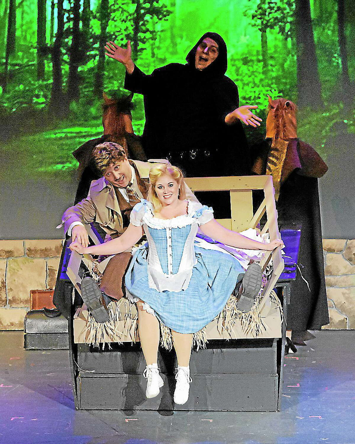 """Submitted photo - Landmark Community Theatre Chuck Stango as Dr. Frankenstein, right, with Katie Brunetto as Inga ride in the hay wagon with Ray Esposito as Igor in the background, in a scene from """"Young Frankenstein"""" at the Thomaston Opera House."""