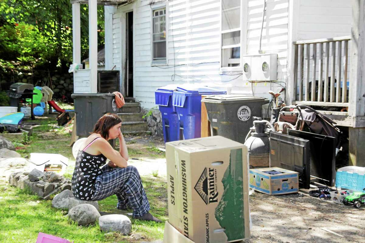 A woman sits in front of a home at 30 South Chapel St. in Torrington, which was badly damaged and deemed unlivable following a two-alarm fire Friday evening.